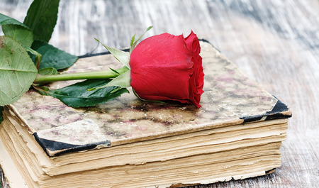 vintage aged closed book on wood desk with rose