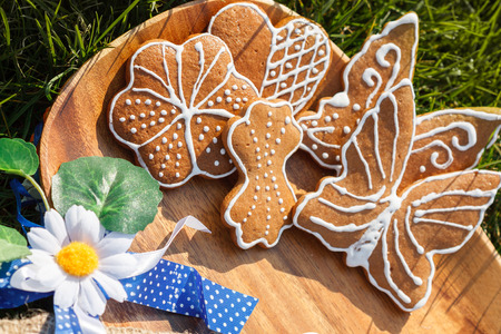 decorated gingerbread on a wooden plate lying in the grass outside with decorative Daisy