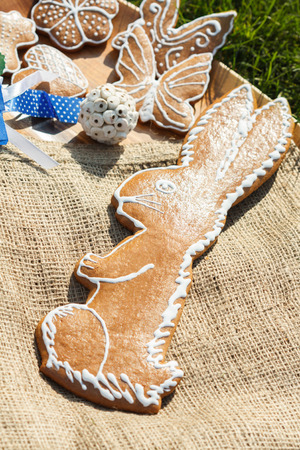 decorated gingerbread - hare on a wooden plate with sackcloth lying in the grass outside with decorative Daisy Stock Photo