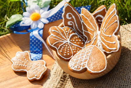 decorated gingerbread on a wooden bowl and plate lying in the grass outside with decorative Daisy