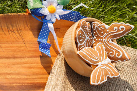 decorated gingerbread on a wooden plate lying in the grass outside with decorative Daisy with copy space