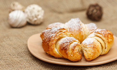 close up of fresh three croissants on plate