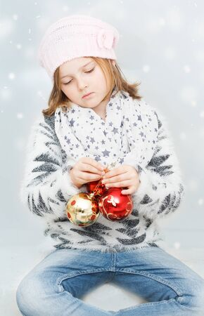 dreamy young girl with Christmas bulbs on winter background - Christmas greeting card