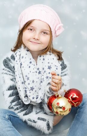 smiling young girl with Christmas bulbs on winter background - Christmas greeting card Stock Photo