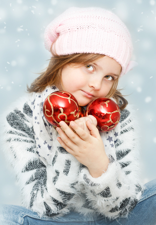 cute young girl with Christmas bulbs on winter background - Christmas greeting card
