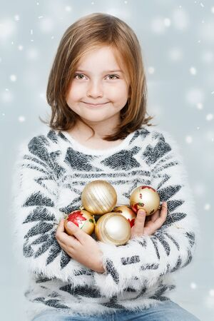 cute young smiling girl with Christmas bulbs on winter background - Christmas greeting card Stock Photo