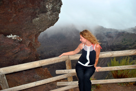 The young beautiful girl at a muzzle of a volcano of Vesuvius. Stock Photo
