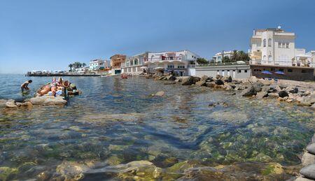Girlfriends sunbathe near the embankment of the Italian resort Santa Marinella