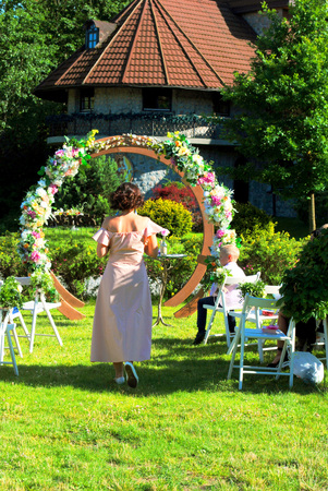 Preparation of a wedding in the open air at a flower arch.