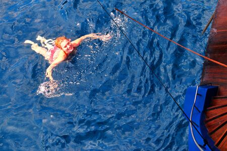 Fit blonde woman enjoying sailing and swimming in the Gulf of Naples basin.