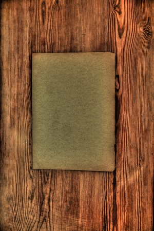 Old grungy paper on wooden background photo