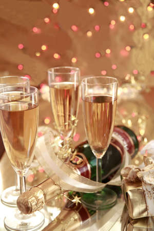 Champagne and gifts on gold background photo