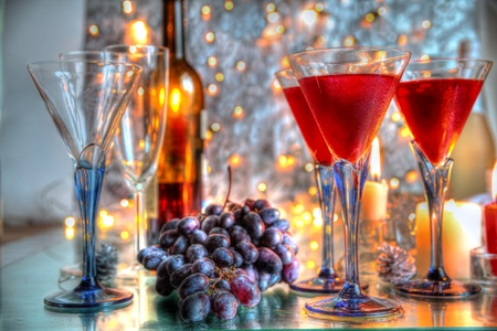 Champagne in glasses,grapes,candles on silver background. photo
