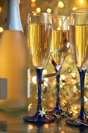 birthday champagne: Close-up of champagne in glasses and blurred lights on gold background. Stock Photo