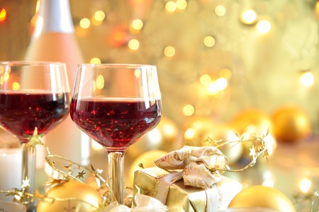 Red wine in glasses on golden background.