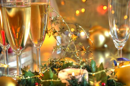 Closeup of champagne in glasses,candle lights,baubles and blurred lights on background. photo
