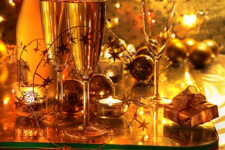 Champagne in glasses and gifts on golden background. photo