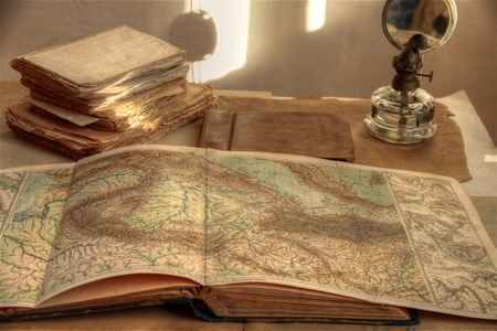 Closeup of old atlas, books and oil lamp.