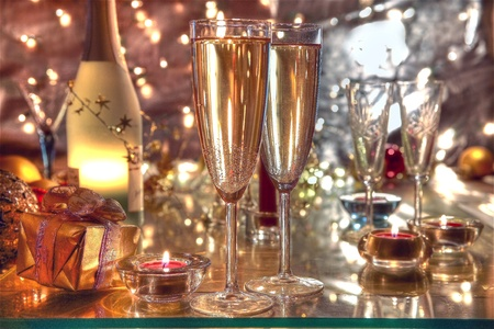 Champagne in glasses,candle and gifts on blurred lights background.