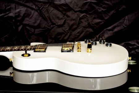 White guitar on dark background.