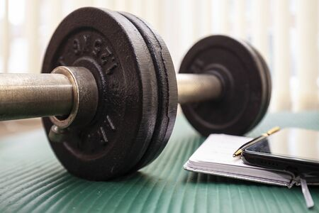 Close-up of dumbbell,notebook, pen and mobile phone.