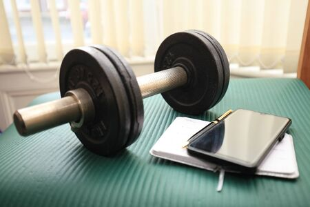 Close-up of dumbbell, mobile phone and notebook.