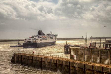 Maneuvering ferry at Dover wharf in stormy weather. A breakwater in the background.