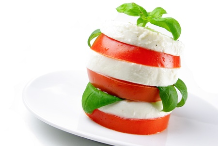 mediterranean cuisine: Tomato and mozzarella slices decorated with basil leaves on a plate and white background