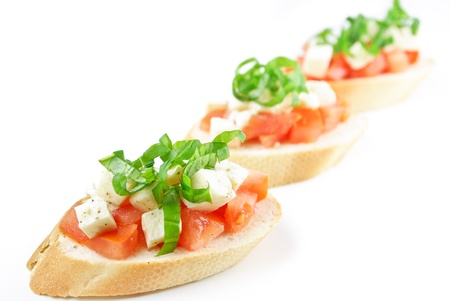 Bruschetta with fresh diced tomatoes, mozzarella and fresh basil isolated on white photo