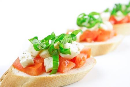 comida gourmet: Bruschetta de tomate fresco picado, mozzarella y albahaca fresca aislados en blanco