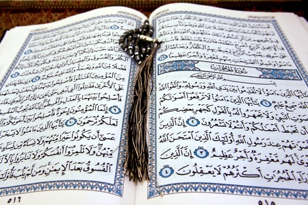 The holy Koran opened with a rosary on it Stock Photo