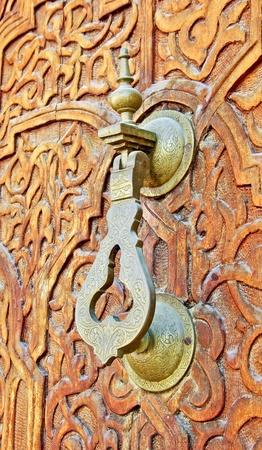 A brass door hammer on a hand carved mosque door Stock Photo