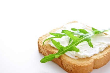A crusty toasted bread whith cheese and rocket salad leaves isolated on a white background