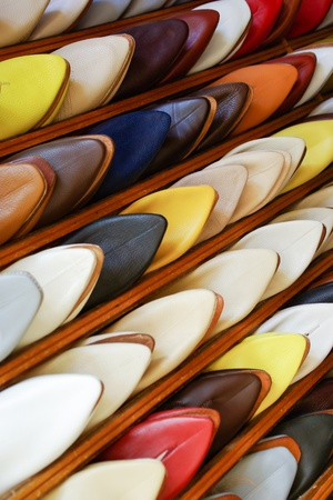 Colorful Moroccan men silppers aligned on a shoe rack in a shop photo