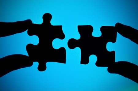 complete solution: two hands connecting two pieces of puzzle