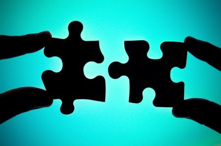 deux mains reliant deux pièces de puzzle Banque d'images