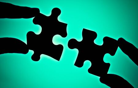 metaphorical: two hands connecting two pieces of puzzle