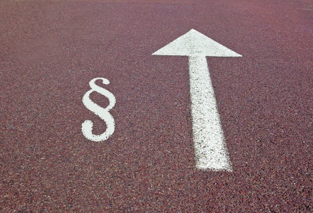 an arrow on the asphalt showing the direction with the law sign near it photo