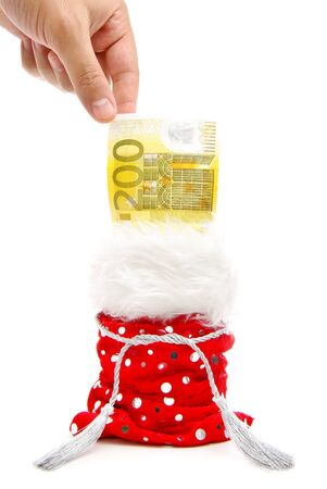 a hand aiming to take a bank note from a red present-bag isolated on a white background photo