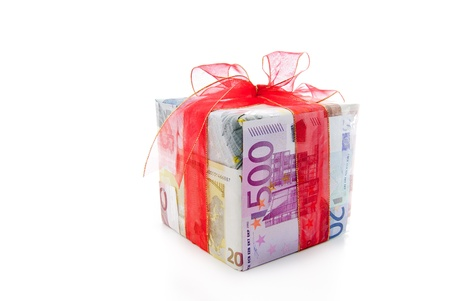 christmas profits: Different euro bills with red ribbon packed as a gift box isolated on a white background