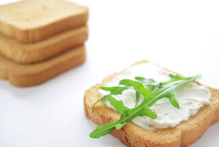 A crusty toasted bread whith cheese and rocket salad leaves and additional bread in the background isolated on a white photo