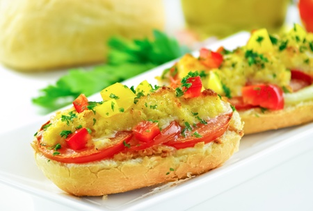 Baked bruschetta with diced vegetables and cheese. Ingeredients in the background