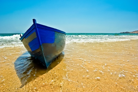 shore line: A traditional fishing boat  ashore at the beach Stock Photo