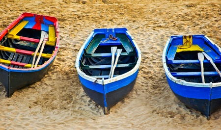 small boat: Three traditional fishing boats on sandy beach
