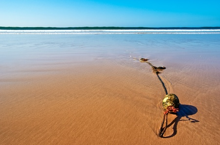 showpiece: An anchor rope with a buoy at a deserted beach