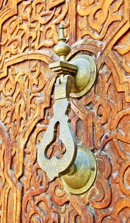 A brass door hammer on a hand carved mosque door photo