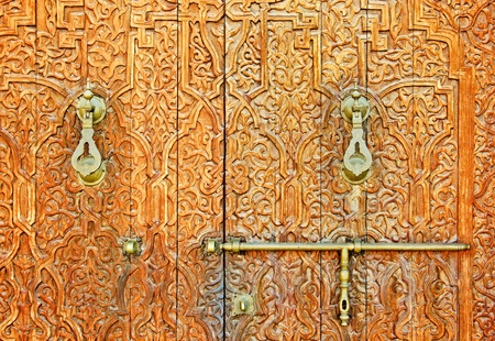 An antique ornate Mosque door with bronze door handles photo
