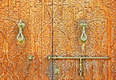 An antique ornate Mosque door with bronze door handles