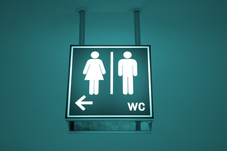 man and women wc sign: Men and women toilet sign with an arrow showing direction Stock Photo