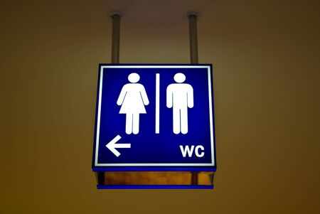 unisex: Men and women toilet sign with an arrow showing direction Stock Photo
